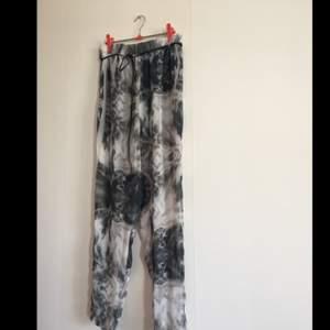 Fräsiga tunna sommarbyxor!  Jättesnyggt mönster i svart och grå/blåa palmblad och fjärdar. Liten riv skada i överkant, se sista bild.