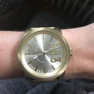 Herrklocka ifrån Diesel i guld färg. Uret är ca 4,5cm. Box och extra länkar finns kvar. Modellen passar även dam om man vill ha en oversized klocka. Sparsamt använd. Jag betalar frakt och har swish.