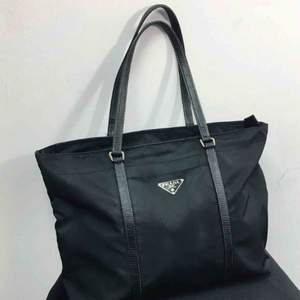 Prada Black Tessuto Nylon Tote Bag. Excellent condition exterior. The interior has been professionally repaired. One internal pocket. 12.75