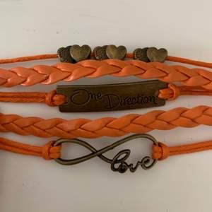 Orange läder(vet ej om det är imitation eller äkta) armband med one direction, justerbart, ej använt, små skav har blivit av att ligga i en låda, färgen visas bäst på första bilden