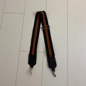Supersnyggt band till en väska i svart och vinrött. Frakt tillkommer