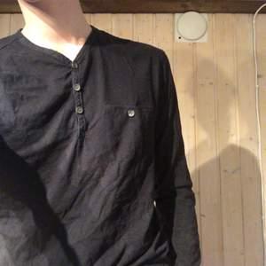 Långärmad tröja med knappar både på halsen och på bröstfickan. Ett riktigt härligt basicplagg. Samfraktar gärna.