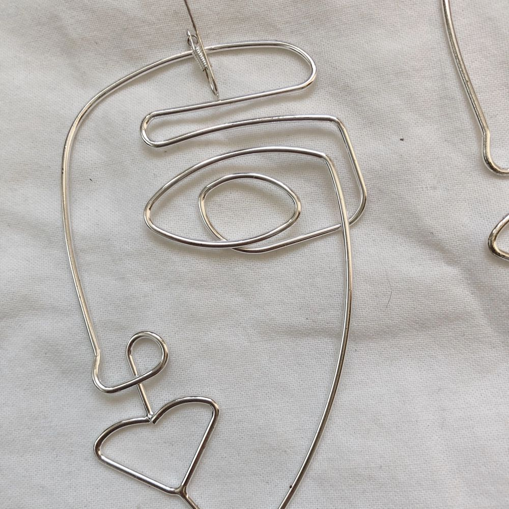 Örhängen med ansikten i ståltråd. Köpta på h&m förra året. 10 cm långa. Använda 2ggr. Frakten ingår i priset. . Accessoarer.