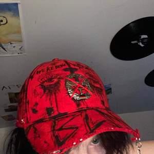 Egendesignad keps med en pin från tysklands flygvapen på huvet. Orginellt så satt den på en av deras hattar så denna keps är unik. Egendesignad märke: We're Being Watched