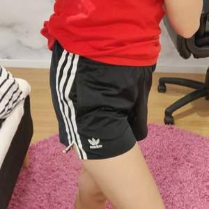 Svarta adidasshorts i träningsmaterial. Stl UK 2, men passar XS. Två fickor framtil och en baktill.