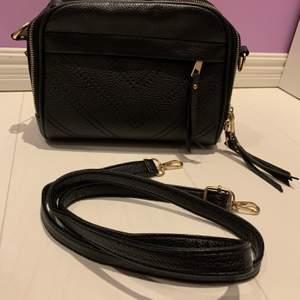 En fin svart väska med små gulddetlajer. Väskan har många dragkedjor samt kan användas på olika sätt. Bra skick och aldrig använd, inkl frakt men inte för dyrt!❤️✨