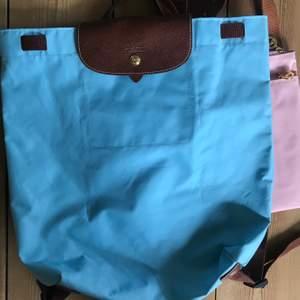 2 äkta longchamp. En ljusblå ryggsäck och en axelväska rosa. Båda i fint skick!