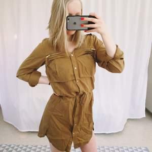 Klänning i khaki grön/brun från H&M. Justerbar midja. Fickor. Man kan knäppa upp klänningen hela vägen. Snugga detaljer i guld.