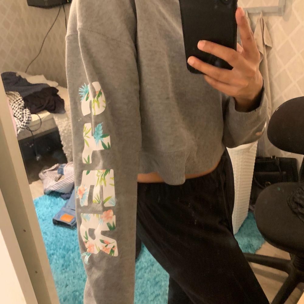 En grå sweartshirt från Hollister, den har tryck på ärmen där det tillsammans ska stå