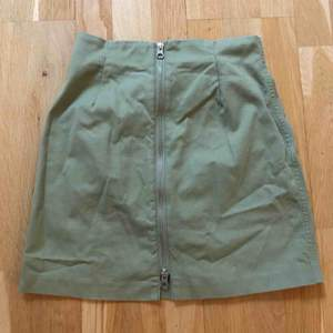 Snygg minikjol i ljusgrönt jeanstyg. Dragkedja framtill