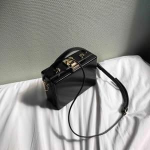 Svart väska i portföljdesign. Väldigt sparsamt använd. Se bilder för insida, storlek och remlängden på väskan. Vid flera köpare så går köpet till högst bud. Möter gärna upp i Stockholm, annars står köparen för tillkommande frakt, 72kr:)