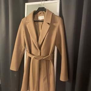 Ljusbrun kappa från Vila i storlek 38, passar perfekt under hösten. Köpt förra hösten och är mycket sparsamt använd. Finns ett bälte till den som även är avtagbart!