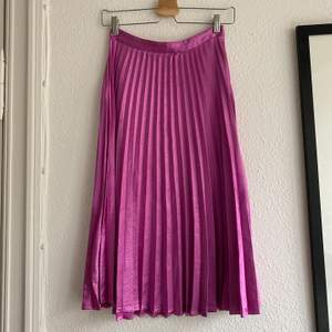 Rosa plisserad kjol från Vero Moda. Stängs med dragkedja på baksidan. Fint skick, tyget är dock lite luddigt/slitet på vissa ställen.