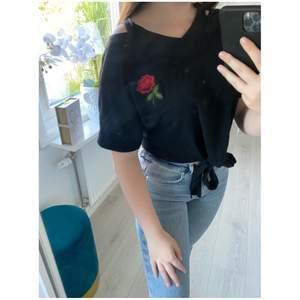 En svart T-shirt med en ros och snygga detaljer på axlarna. T-shirten är i storlek S och är knappt använd.