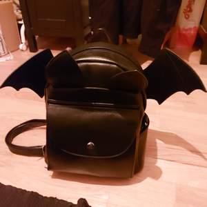 Svart fladdermus ryggsäck med avtagbara vingar.