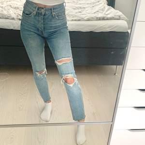 Ett par ljusblåa jeans med slitningar i perfekt passform ✨ Lagom högmidjade och tighta, rå kant nertill. Passar någon runt 160cm. Skicket är jättebra! (Nypris 499kr) (Mitt innebensmått är ca 77cm)