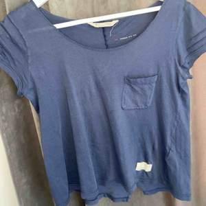En blå t-skirt med en ficka på bröstet, använd en gång och är verkligen suuuperfin 💕 jag köpte den för ett år sedan för 600kr :)