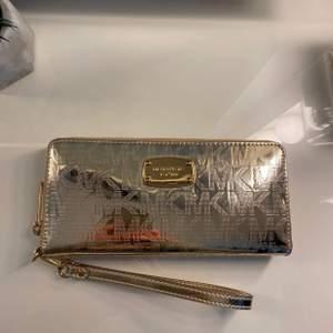 Galet snygg guld glansig Michael Kors plånbok. Nyskick, inga skråmor osv, knappt använd. Får plats med ca 20 kort. ORGINALPRIS: 1100 kr