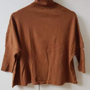 Tunnstickad brun polotröja med ljusblå detalj vid halsen. 60% ull, 30% silke, 10% cashmere. Mycket bra skick, använd en gång. Normal strl. M.