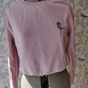 Rosa tröja från HM med briderat rosmitiv på bröstet. Bra skick, 50kr +frakt