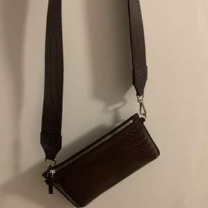 En helt oanvänd väska i brun fake läder tyg ifrån Carin Wester. Bandet ingår till väskan