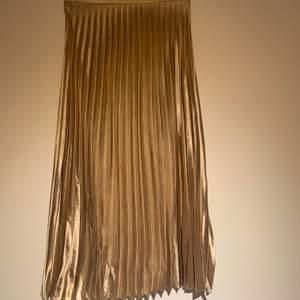 En jättefin guld kjol i jättebra skick! Den är väldigt lång jag är 175cm och den når ner till mina anklar, högmidjad och väldigt bekväm🌟🌟 köparen står för frakt