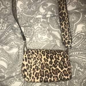 Oanvänd leopard väska med leopard band