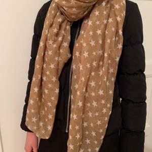 Beige/brun halsduk/sjal med vita stjärnor på. Extra fin såhär i juletid!