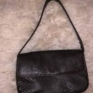En fin baguettebag med imitation av ormskinn. Passar mycket bra till allt från vardag till fester!