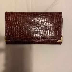 Säljer denna vinröda plånbok. Den har guld detaljer. Den är i jätte bra skick. Undrar man över något så är det bara att kontakta mig.