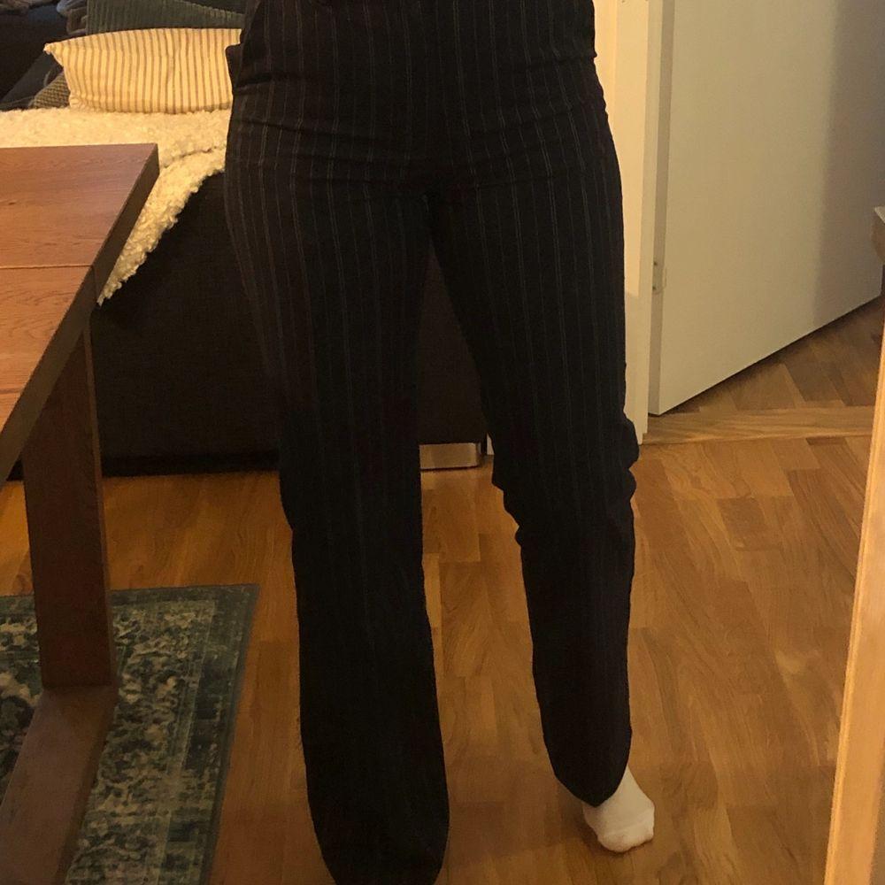 Mörkblå randiga kostymbyxor i mjukt tyg. Vida ner till, något längre i benen. Strlk 34, använda 1 gång. Kan mötas upp eller skickas . Jeans & Byxor.