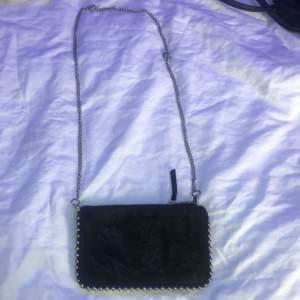 En svart väska ifrån Zara. Silvriga detaljer! 2 fack i väskan. köparen står för frakt. Säljs pga använd få gånger