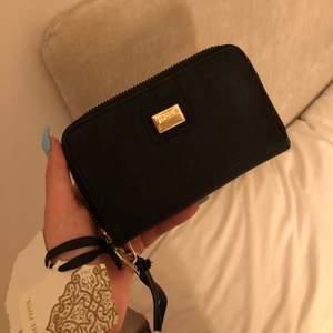 Svart plånbok med guld detaljer, helt oanvänd.