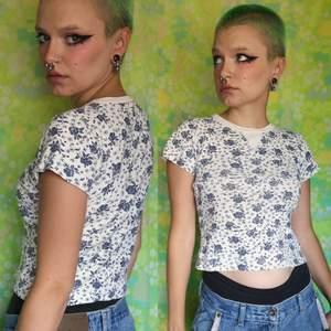 Benvit/beige blommig kortare t-shirt, blommorna är ljusare blå i verkligheten än på bild. I använt men bra skick, kan inte garantera äkthet då den är köpt secondhand. Frakten ligger på 48 kr, samfraktar gärna😊👍