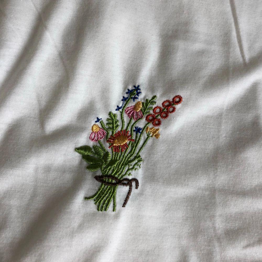supersöt aesthetic t-shirt med en broderad bukett på bröstet. Oanvänd! Köpt från soaestheticshop. (Inte jag på bilden, men skriv om du vill ha bilder!). T-shirts.