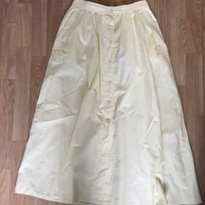Ljusgul A-linjeformad kjol med knappar fram.