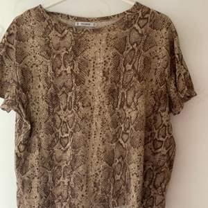 T-shirt med reptil-print från Pull & bear. Strl xs men passar mig med S/M också