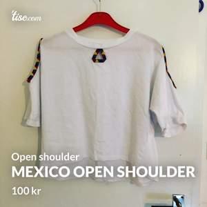 Latinamerikansk top med öppning för axlar samt en öppning framtill som detalj i form av triangel. Aldrig använd. Legat och ekat i byrån i flera år.