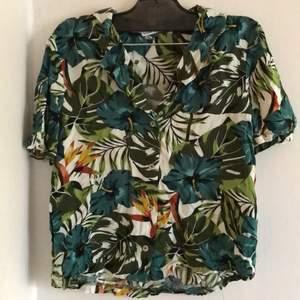 Skjortan är köpt i barcelona. Det är ett svalt material  som har växter på. Kragen är V ringad. Det blir väldigt fint med en polotröja under. Den är lite skrynklig och är andvänd 2 gånger