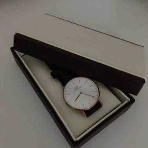 Klocka från Daniel Wellington i roséguld med svart läderband. Relativt använd. Frakt är inkluderat i priset.