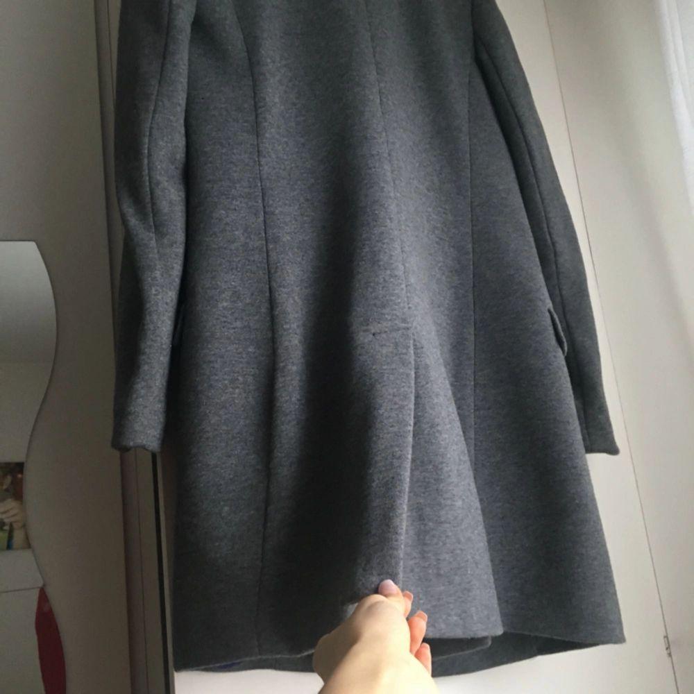 Ursnygg grå trendig kappa som knappt är använd! Sitter tight och formar kroppen snyggt! Inga skador, som ny! . Jackor.