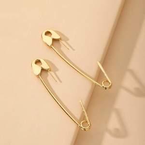 Oanvända örhängen som ser ut som säkerhetsnålar