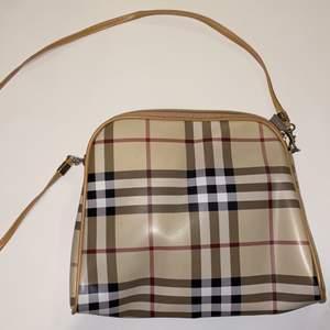 """Fin väska med burberry """"mönster"""". Långt, smalt, avtagningsbart band. Lite slitningar som syns på andra och tredje bilden"""