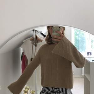 En jättefin beige brun stickad tröja ifrån Naked med vida armar. Endast använd 1 gång så typ som ny.
