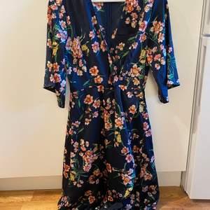 Mörkblå långklänning med blommor, silkematerial. Använt 1 gång och är i bra skick. Nypris 500. Frakt ingår i priset