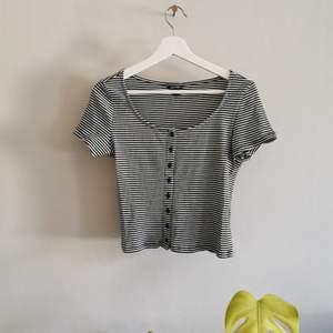 Söt tshirt med knappar från Monki. Köparen står för frakt.