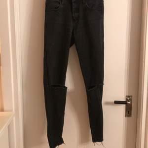 Ett par grå/svarta högmidjade jeans med hål på knäna och lite fransigt längst ner. I använt skick. Mötes upp i centrala Uppsala alt frakt som köpare står för