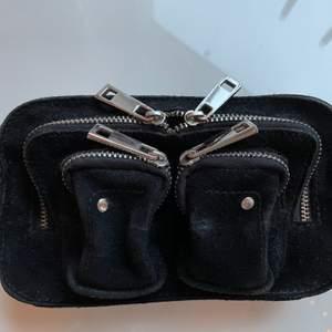 Svart liten väska från nunoo. Mycket använd men fortfarande i okej skick. Ett längre mocca band och en kedja medföljer. Nypris: 1099kr.