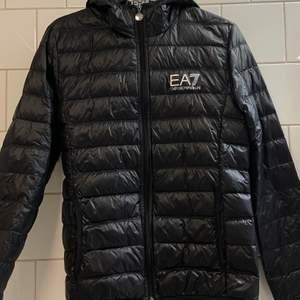 EA7 jacka i storlek S. Knappast använd men det finns ett jack på insidan av jackan ungefär vid EA7 lappen som syns på den andra bilden. Orginalpris 1600 kr. Frakt ingår ej i priset