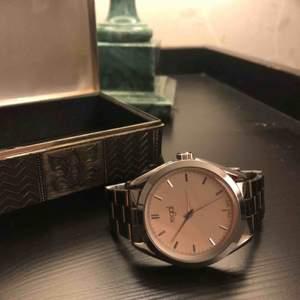 Silverfärgad klocka från regal. Reglerbar storlek.  Batteri måste bytas. Frakt tillkommer